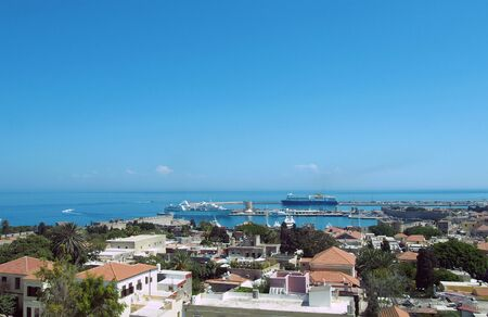 a panoramic view of rhodes town with buildings of the city and old walls around the harbor with ships and boats next to a blue summer sea Фото со стока