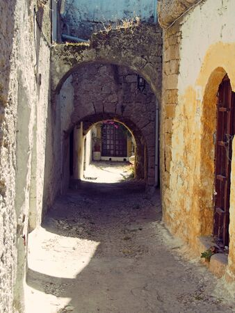 an alley between ancient buildings in rhodes town with low arches and doorways