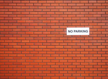 a white sign saying no parking on a red brick wall