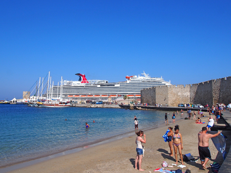 rhodes town, rhodes, greece - 07 september 2017: tourists on the beach near rhodes town harbor with the cruise ship carnival vista moored behind the fort