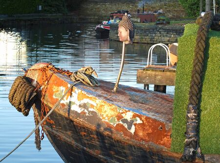 The bow of an old rusty iron canal boat with an old Buddha head moored with ropes on a jetty with reflections in dark water