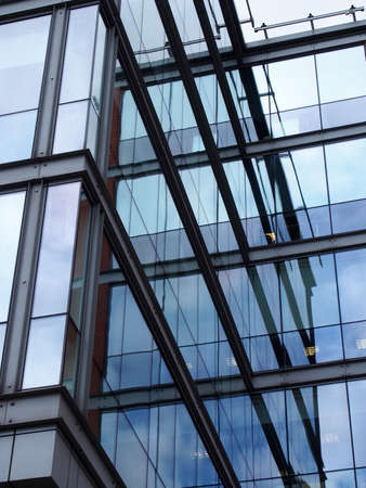 a full frame modern office architecture abstract with geometric shapes and buildings and sky reflected in blue glass windows