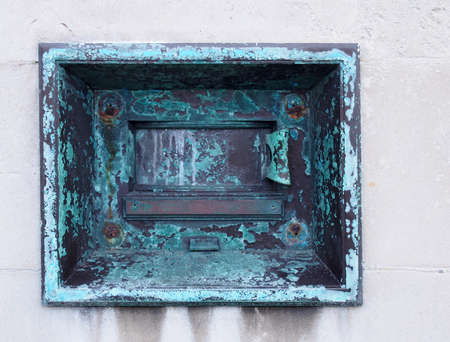 an old metal outdoor overnight deposit box also known as a night safe, once common on the outside walls of banks