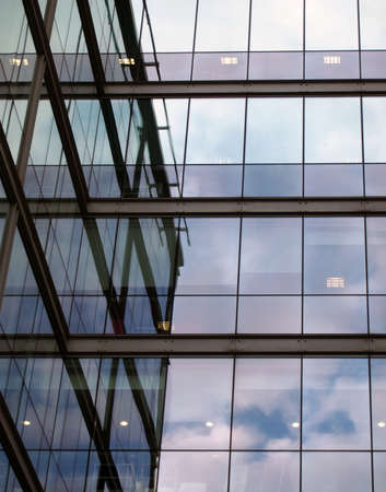 a full frame modern office architecture abstract with geometric shapes and clouds reflected in blue glass windows Stock Photo