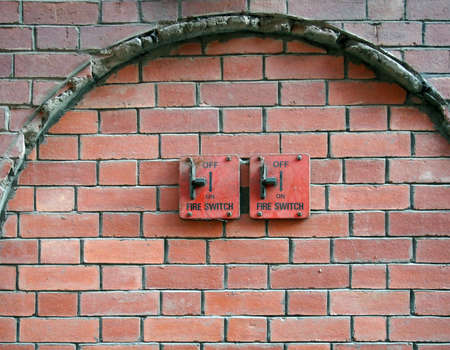two old red metal fire switches on an exterior brick wall