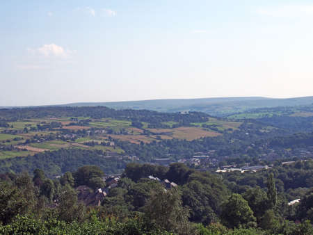 a panoramic view west yorkshire countryside with the village of warley surrounded by woodland and farmland with pennine hills in the distance