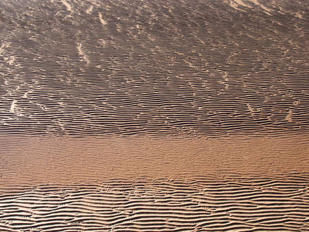 full frame beach background with wavy patterned surface formed on the wet sand and shadows with a strip of water running across image