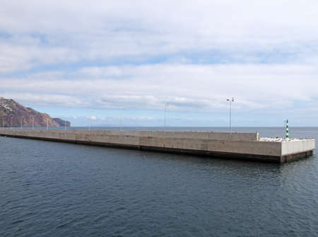 the long concrete harbour wall surrounding the marina and docks in funchal madeira with the buildings of the town in the distance