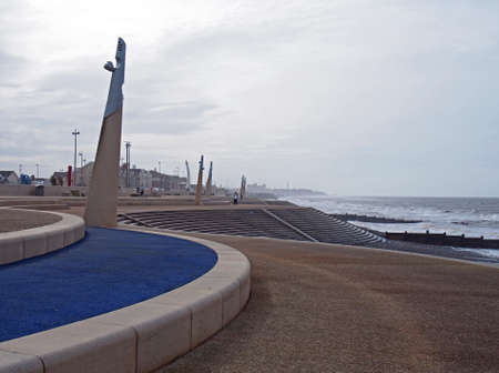 Blackpool, Lancashire, United Kingdom - 6 March 2020: The curved promenade along the seafront at cleveleys in blackpool with steps leading to the beach with town buildings in the distance Editorial