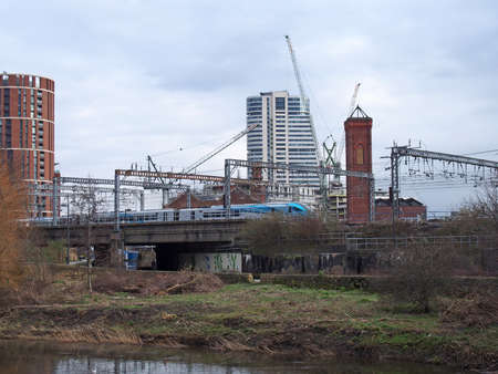 leeds / united kingdom - 04 March 2020: the river aire in leeds taken from the footpath showing the south bank and holbeck with a train on the railway tracks in between