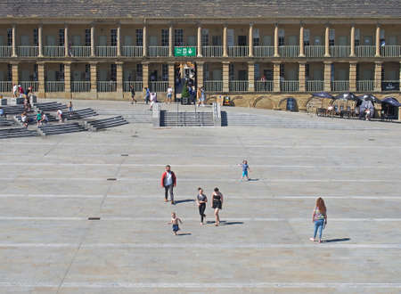halifax, west yorkshire, united kingdom - 23 july 2019: people relaxing and enjoying the summer sunshine in cafes and on the steps in the square of halifax piece hall in west yorkshire Editorial