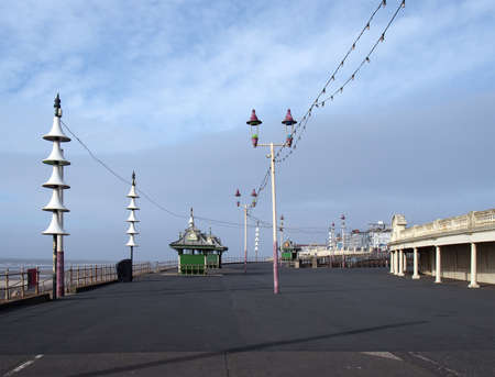 a view along the pedestrian promenade in blackpool with traditional wooden shelters and lights with the town buildings in the distance Editorial