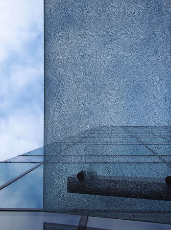 a pane of shattered glass in front of a modern office building with straight edge dividing the image against a blue cloudy sky