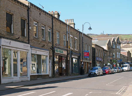 hebden bridge, west yorkshire / united kingdom - 20 May 2020: crown street in the centre of hebden bridge with shops and cafes at the side of the road