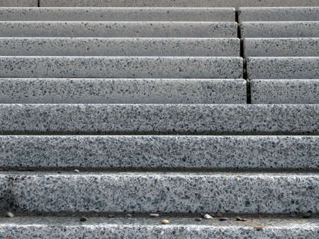 grey textures outdoor concrete stairs with small pebbles on the bottom step