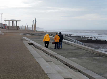 Blackpool, Lancashire, United Kingdom - 6 March 2020: older people in anoraks walking along the promenade along the seafront at cleveleys in blackpool with steps leading to the sea with the town in the distance