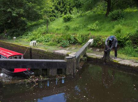 hebden bridge, west yorkshire, united kingdom - 16 june 2019: a woman opening a lock gate on the rochdale canal in hebden bridge west yorkshire