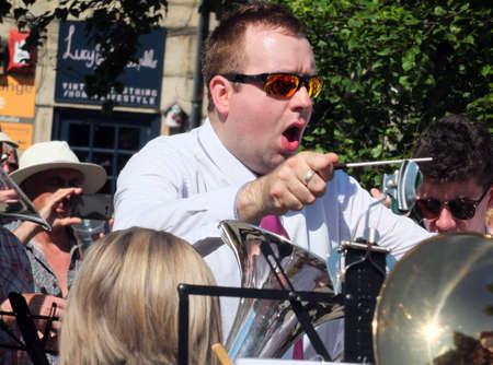 hebden bridge, west yorkshire, united kingdom - 18 june 2017: a close up of the conductor and musicians of a brass band performing at the public brass march contest in hebden bridge town center