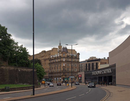 bradford, west yorkshire, united kingdom - 19 june 2019: traffic on hall ings road in bradford with people walking past the car park entrance to the broadway shopping centre
