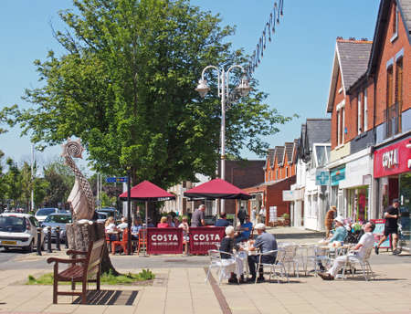 formby, merseyside, united lingdom - 28 june 2019: people sat outside cafes on the high street in summer in formby merseyside