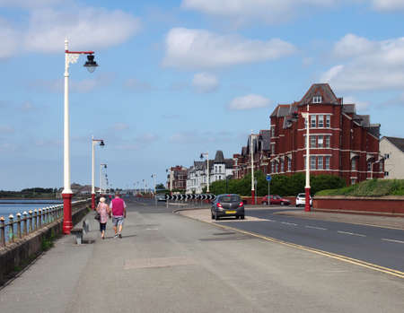 southport, merseyside, united kingdom - 28 june 2019: an older couple walking down marine drive in southport merseyside with old hotel buildings lining the street on a bright summer day