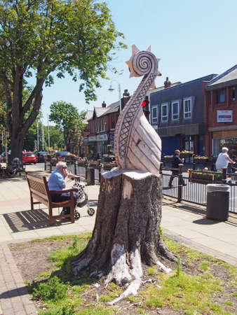 formby, merseyside, united kingdom - 28 june 2019: people crossing the road and sittong on benches on the high street in summer in formby merseyside