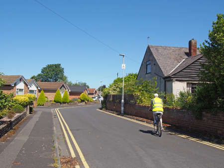 formby, merseyside, united kingdom - 28 june 2019: a man riding a bicycle wearing a reflective vest down a street of typical english suburban bungalows in formby merseyside