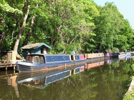 old canal boats moored on the rochdale canal near hebden bridge surrounded by trees in summer sunlight 免版税图像