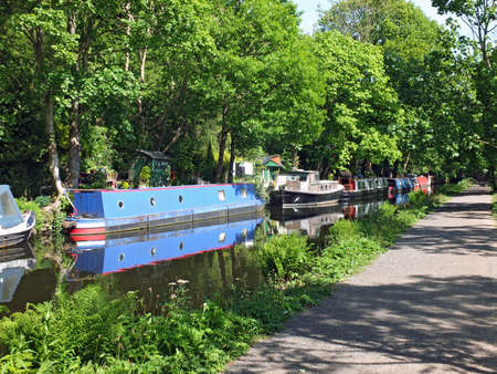 canal boats moored opposite the path on the rochdale canal near hebden bridge surrounded by trees in summer sunlight 免版税图像