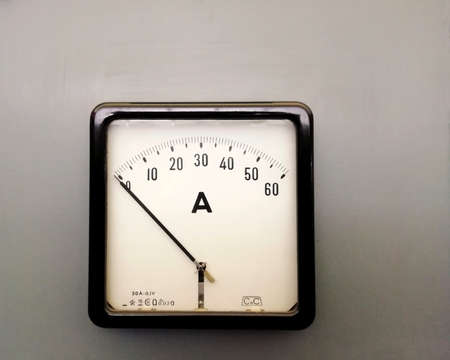 a large square industrial ammeter with an analogue dial with numbers with standard electrical symbols on a white dial on a grey background