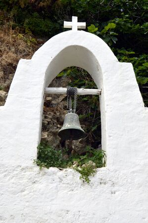bell tower: A small white bell tower with a bell.
