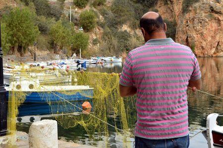 floats: Repair of fishing net in a Greek port.