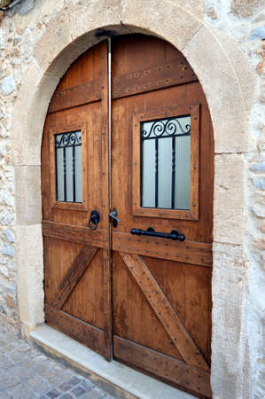 achitectural: A double dark wooden door on a stony wall with an arch, a window and bars.