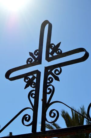 black metal: A cross on a black metal wall.
