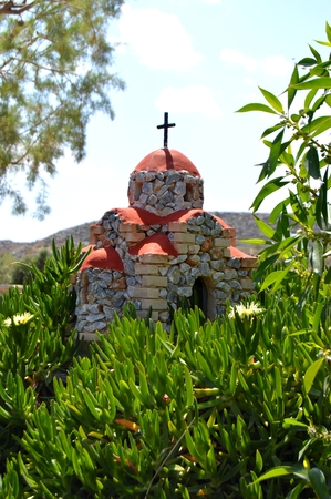 crucify: Reproduction of a church on a hillock with plants crawling. Stock Photo