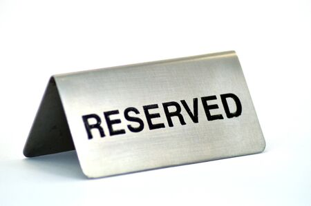 reservation: Plate of reservation of table of aluminum restaurant on white bottom.
