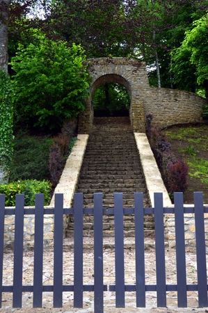 rises: Entrance of a military cemetery to the nature with a stone staircase which rises.