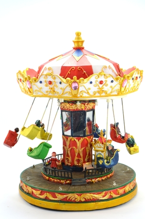Wooden carousel of Christmas with small seats and lively colors. Stock Photo