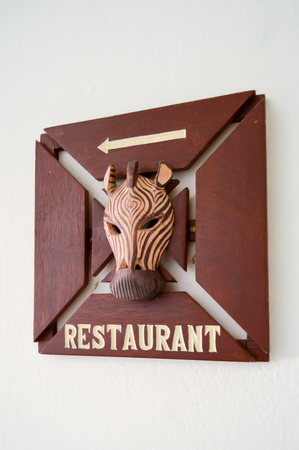 Wooden restaurant sign with a zebra head and a white arrow Banque d'images
