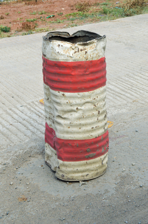 Old iron barrel painted red and white for reporting work on a road in Kenya