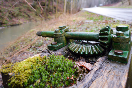 Old green gear on a small wooden lock of a small creek in Luxembourg