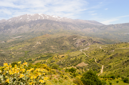 Winding road in the mountain of the center of Crete with the snowy ida mountain Stock Photo