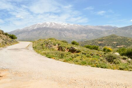 Winding road in the mountain of the center of Crete with the snowy ida mountain Imagens