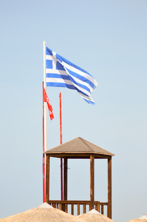 Greek flag floating on a white mat near a guard post on the beach of Amoudara on the island of Crete