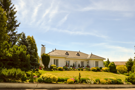Large white house with two porticos and a beautiful flower garden