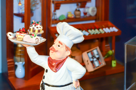 Effigy of a chief cook carrying a tray of cakes in a restaurant in black forest Stock Photo
