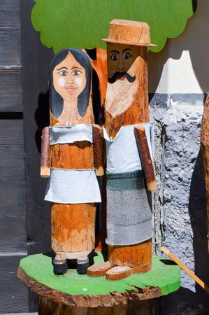 Elderly couple replicated in tree trunks of tyrol in Austria