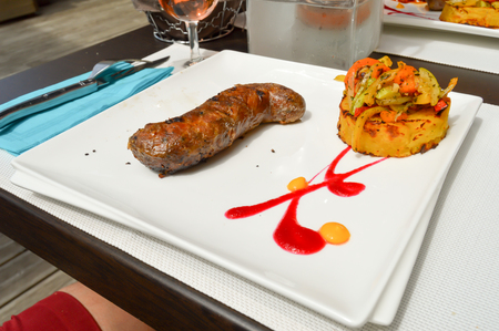 Andouillette served with a potato cake and a nicoise salad in the town of Bar le Duc in Meuse Fran�aise
