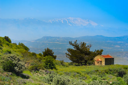 Small chapel on a hill with ida snowy mountain in the background on the island of Crete Editorial