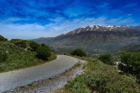 Winding road in the mountain of the center of Crete with the snowy ida mountain Banco de Imagens